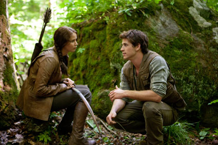 jennifer lawrence and liam hemsworth as katniss and gael in the woods in the hunger games film 2012