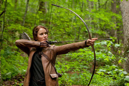 Katniss with bow and arrow in the woods, picture from The Hunger Games